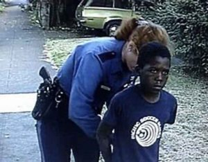 A Child being Handcuffed by a Police Officer