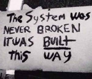 """Hand-lettered sign reading """"The System was never broken; it was Built this way""""."""